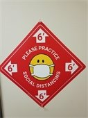 Red sign: please practice social distancing