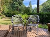 Two chairs on a patio in a summer backyard