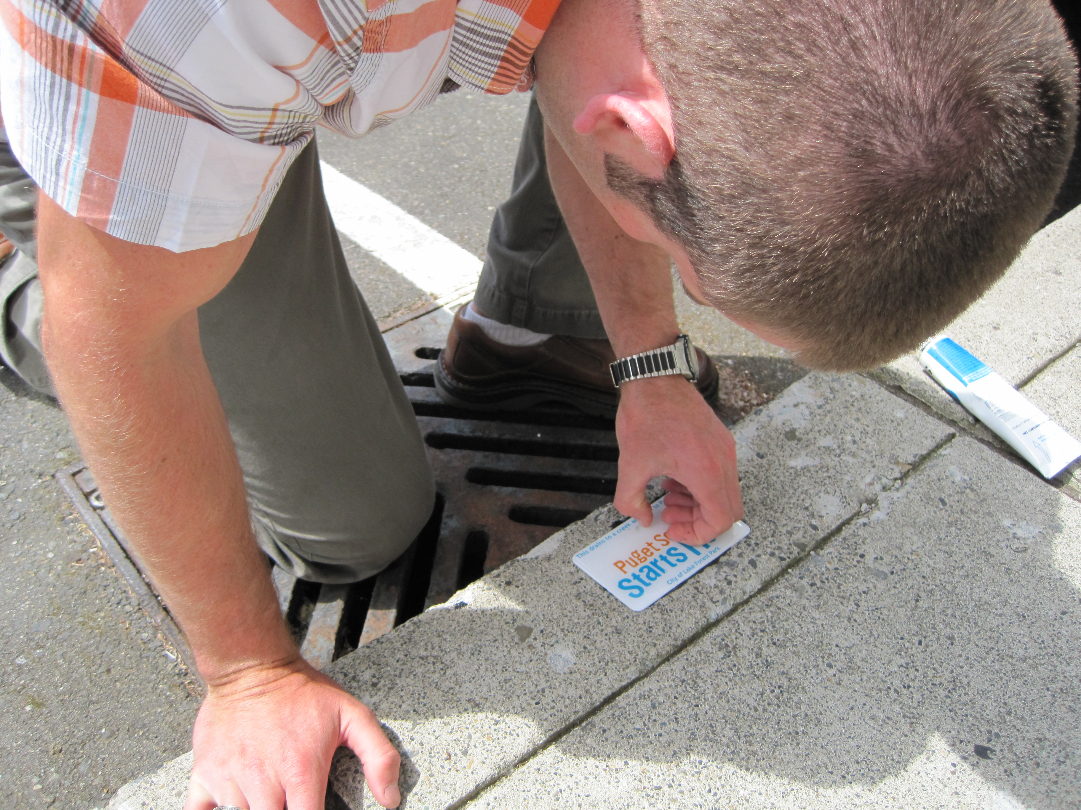 Staff applying storm drain label
